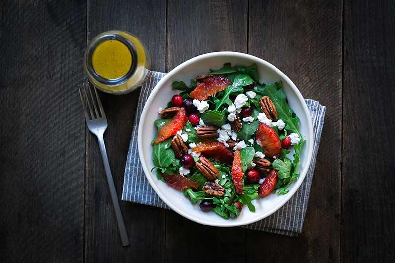 Finished salad next to bottle of orange vinaigrette