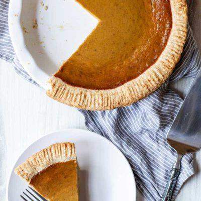 Overhead photo of pumpkin pie from scratch in a pie dish next to a slice of pumpkin pie