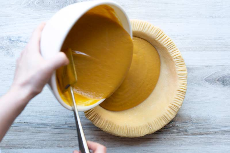 action shot pouring pumpkin pie filling into pie crust.
