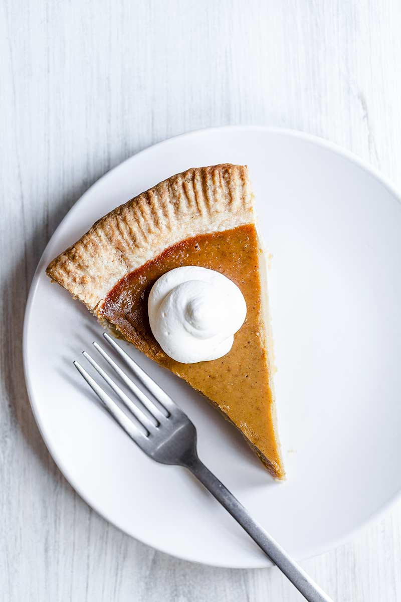 A slice of homemade pumpkin pie topped with whipped cream