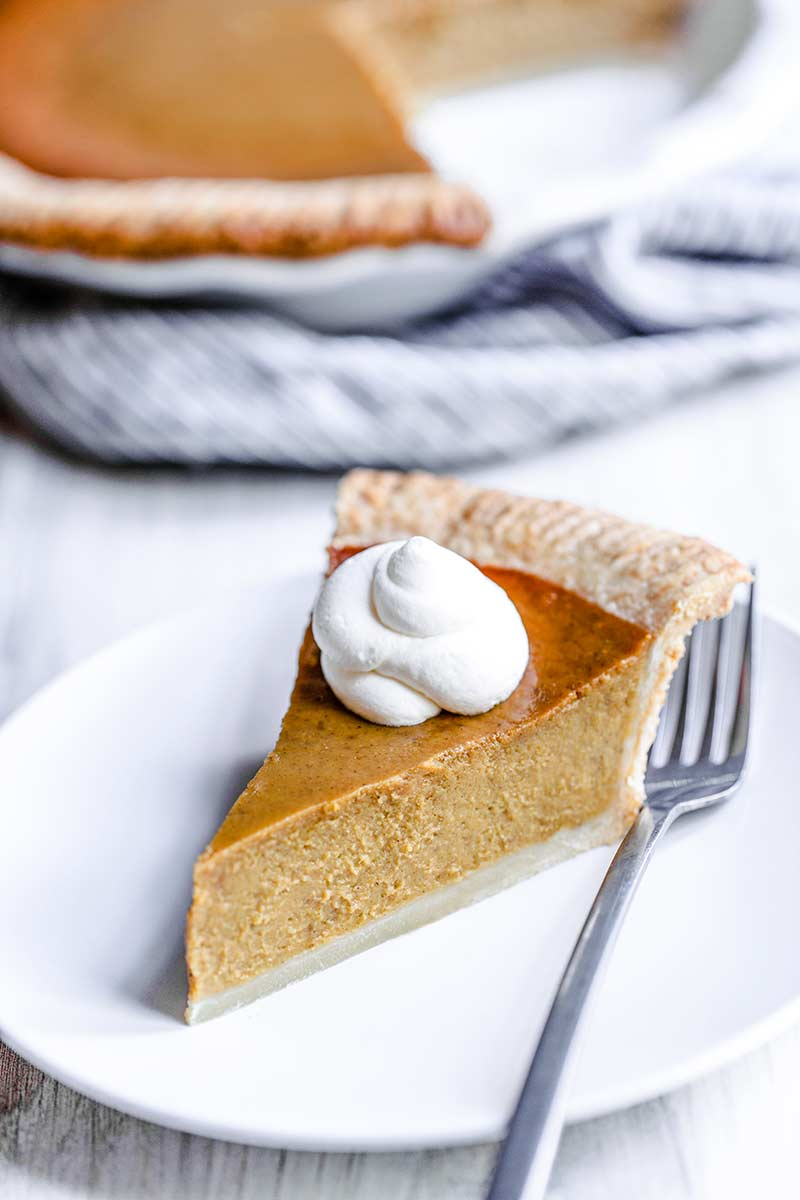 a slice of homemade pumpkin pie from scratch topped with whipped cream.