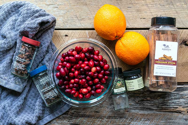 Ingredients for stovetop potpourri spread out, including cranberries, oranges and whole spices
