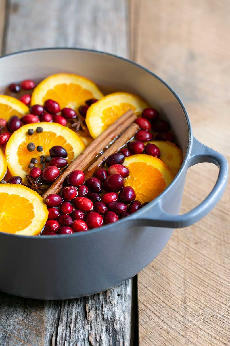 pot of orange slices, cinnamon and fresh cranberries, ready for simmering
