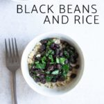Black beans and rice in a bowl next to a fork.