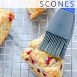 A pastry brush brushing glaze onto cranberry orange scones.