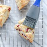 A pastry brush brushing glaze onto cranberry orange scones recipe.