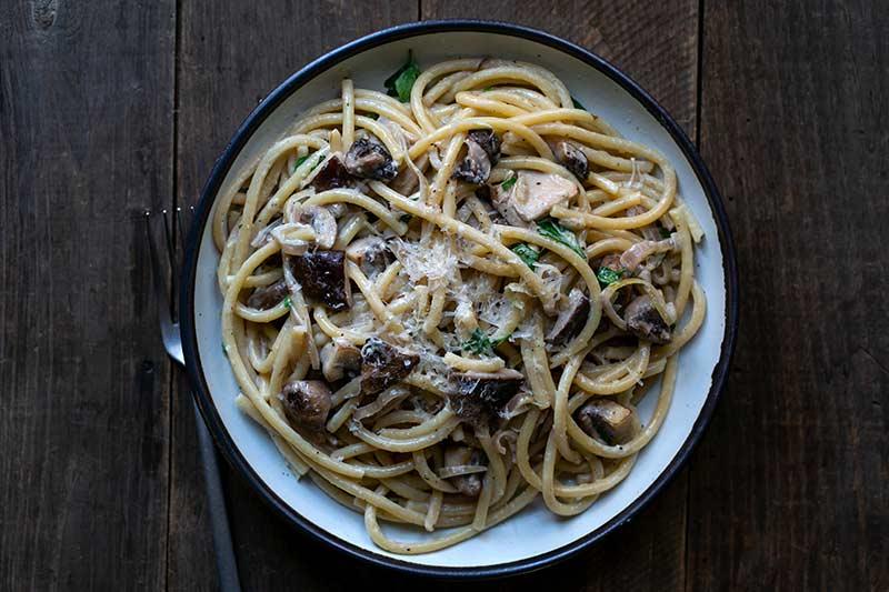 Creamy mushroom pasta recipe on a plate next to a fork