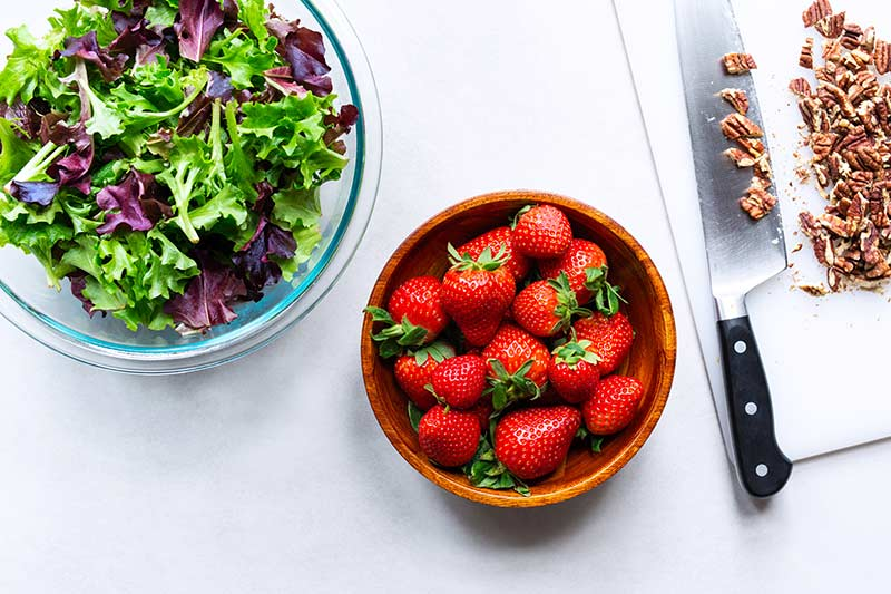 A bowl of strawberries next to a bowl of mixed greens and a cutting board with chopped pecans and a knife.