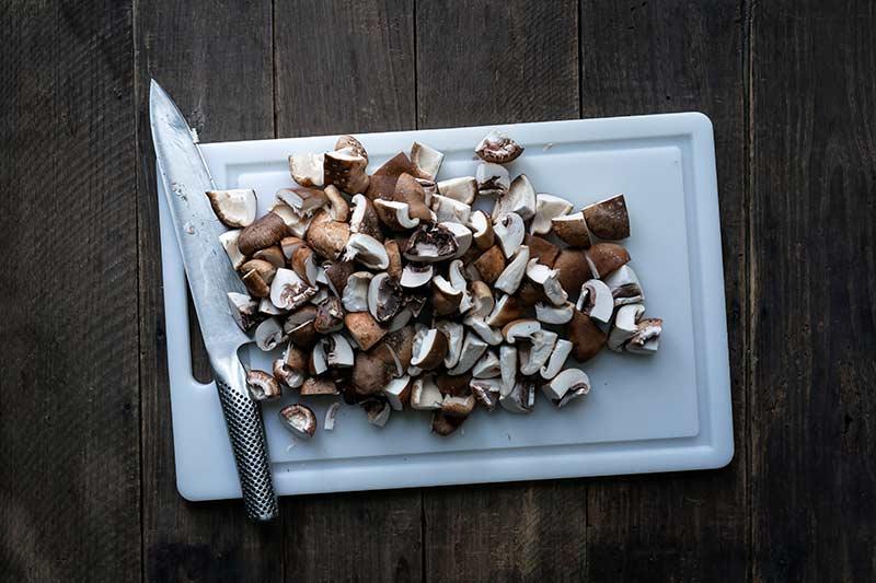Chopped mushrooms on a cutting board.