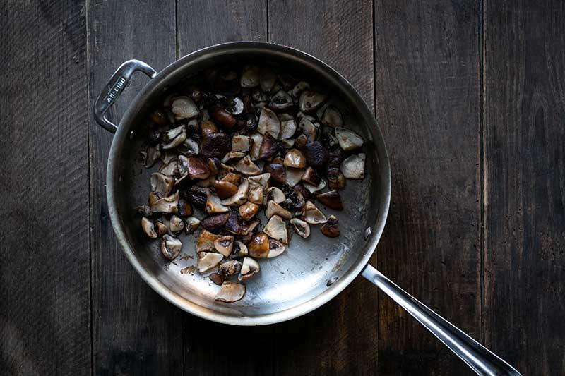 Sautéing mushrooms in a flat-sided skillet until brown.