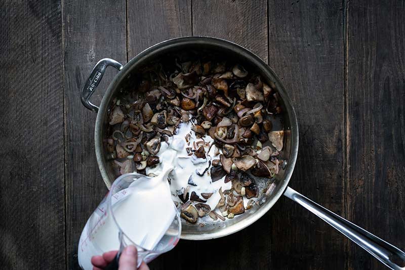 A hand pouring cream into the mushrooms and shallots.