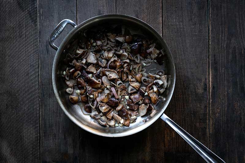 Sautéing shallots alongside the mushrooms.