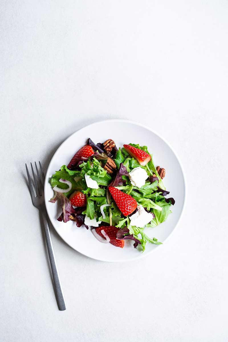 Strawberry salad topped with pickled shallots and feta cheese on a white plate.