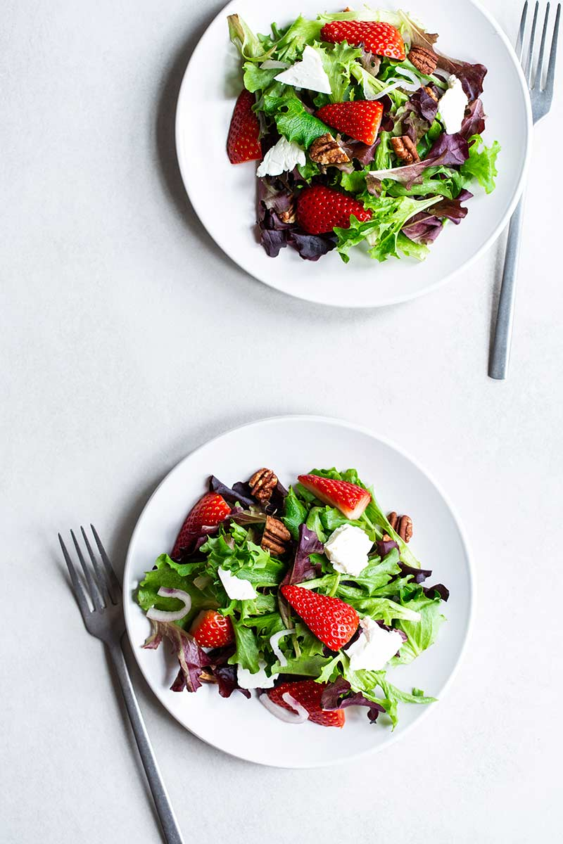 Mixed greens salad with strawberries, pecans and feta on a plate with a fork.