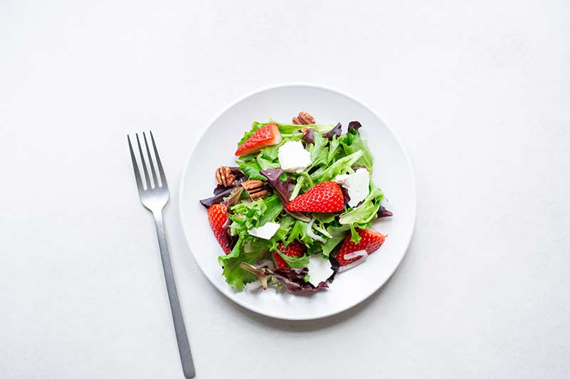 Mixed greens with strawberries, pecans and feta on a plate with a fork.
