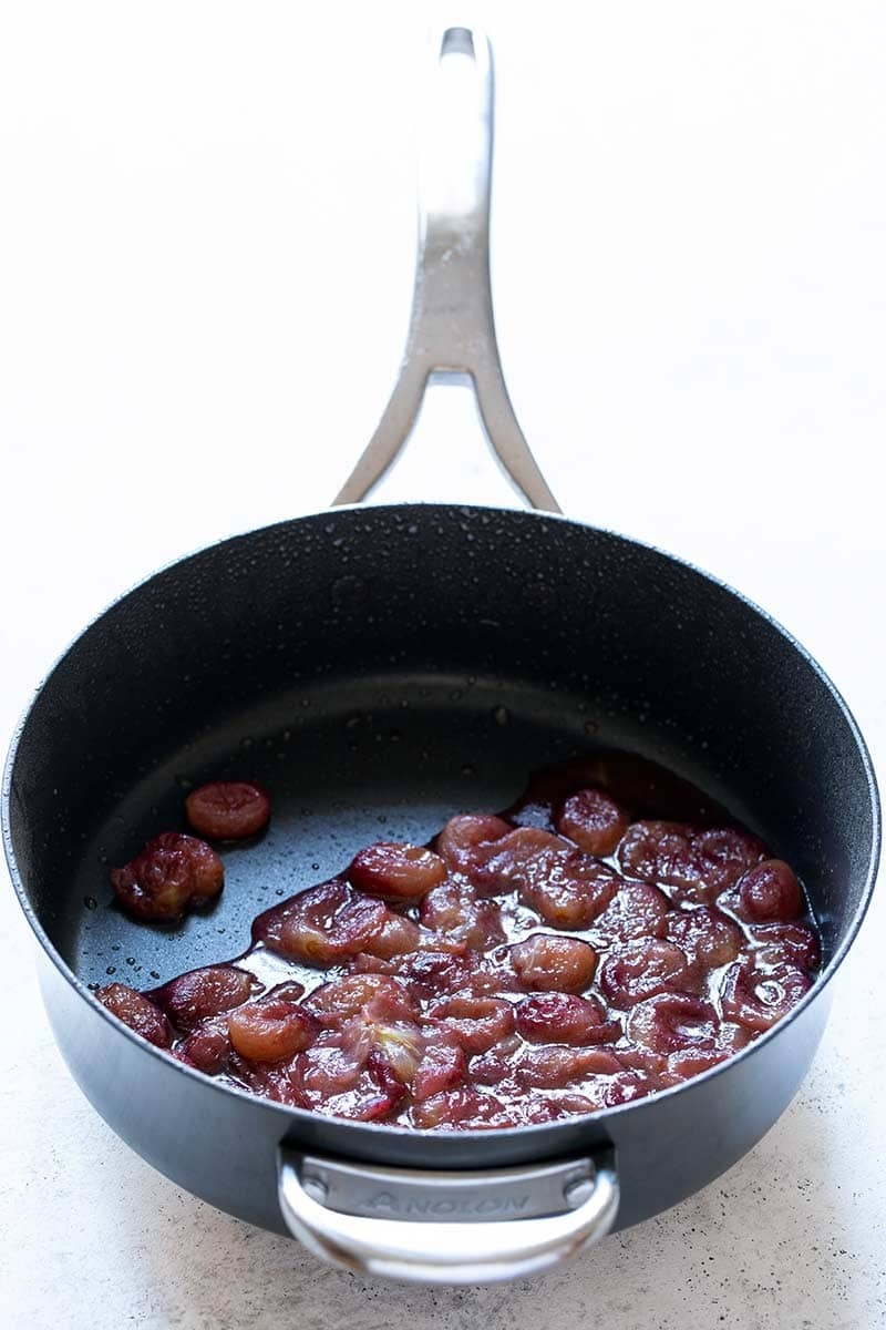 grapes cooked in a skillet until soft and juicy.