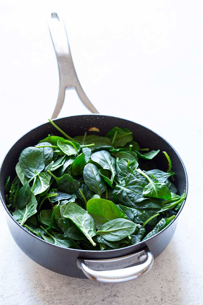 Spinach added to the skillet, all the way to the top.