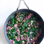 Sautéed spinach with grapes and almonds in a skillet shot from overhead
