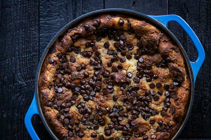 Croissant bread pudding in a round blue baking dish.
