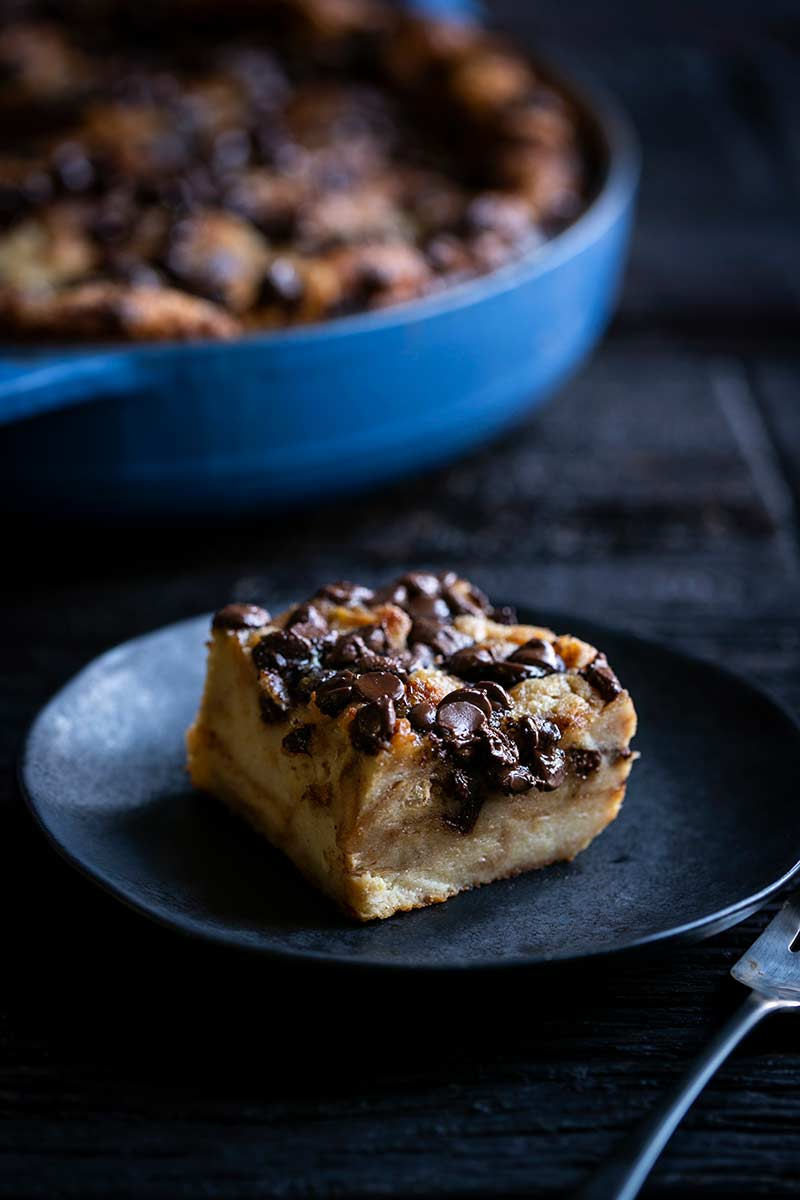 A slice of chocolate croissant bread pudding on a plate.