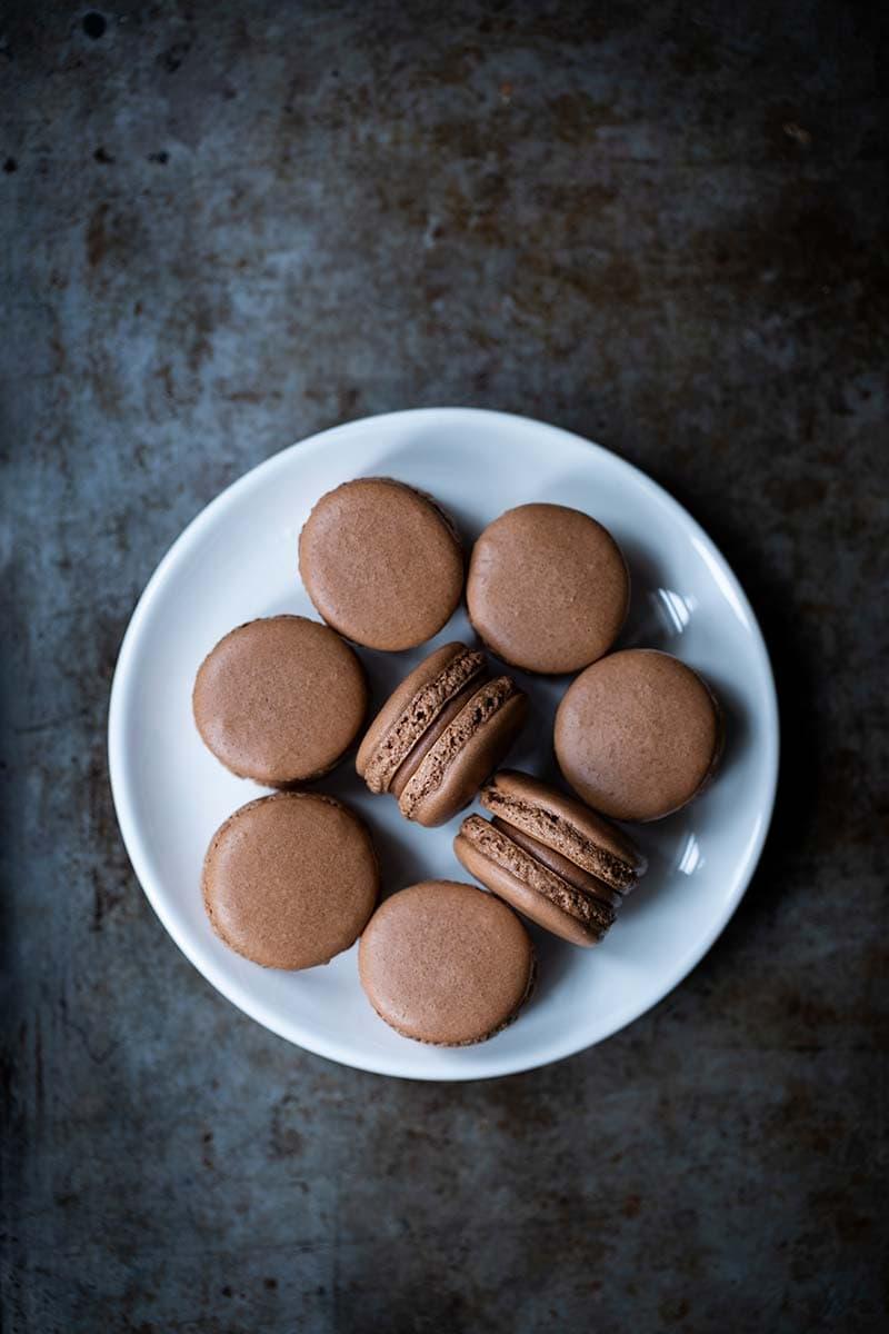 Sea salt chocolate macarons on a white plate