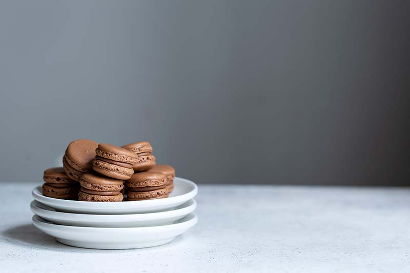 Chocolate macarons stacked up on a plate