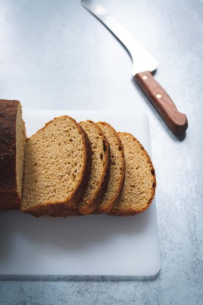 Sliced oatmeal molasses bread on a cutting board