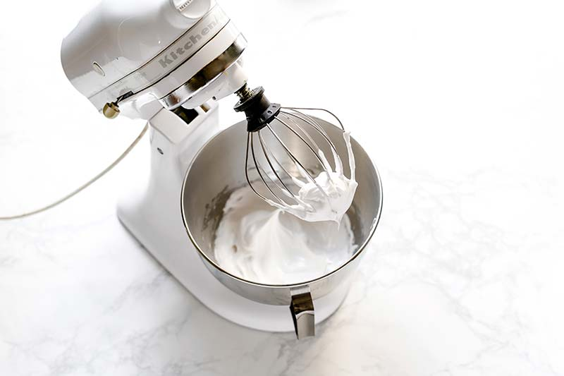 Egg whites whipped to a stiff peak in a stand mixer