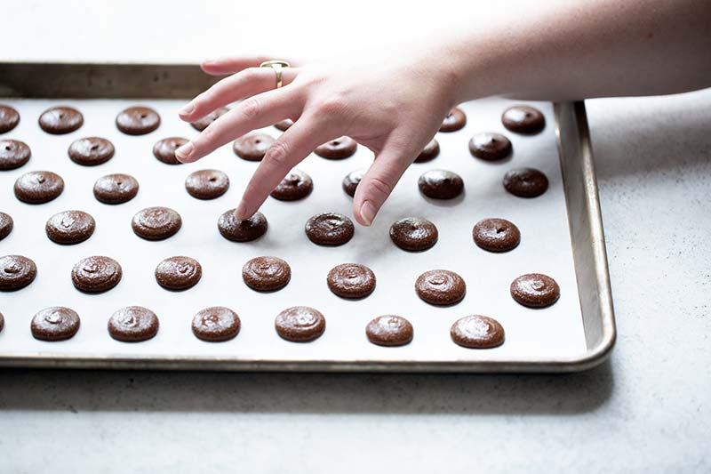 Using fingers to dab water on top of the unbaked chocolate macarons to smooth out the top