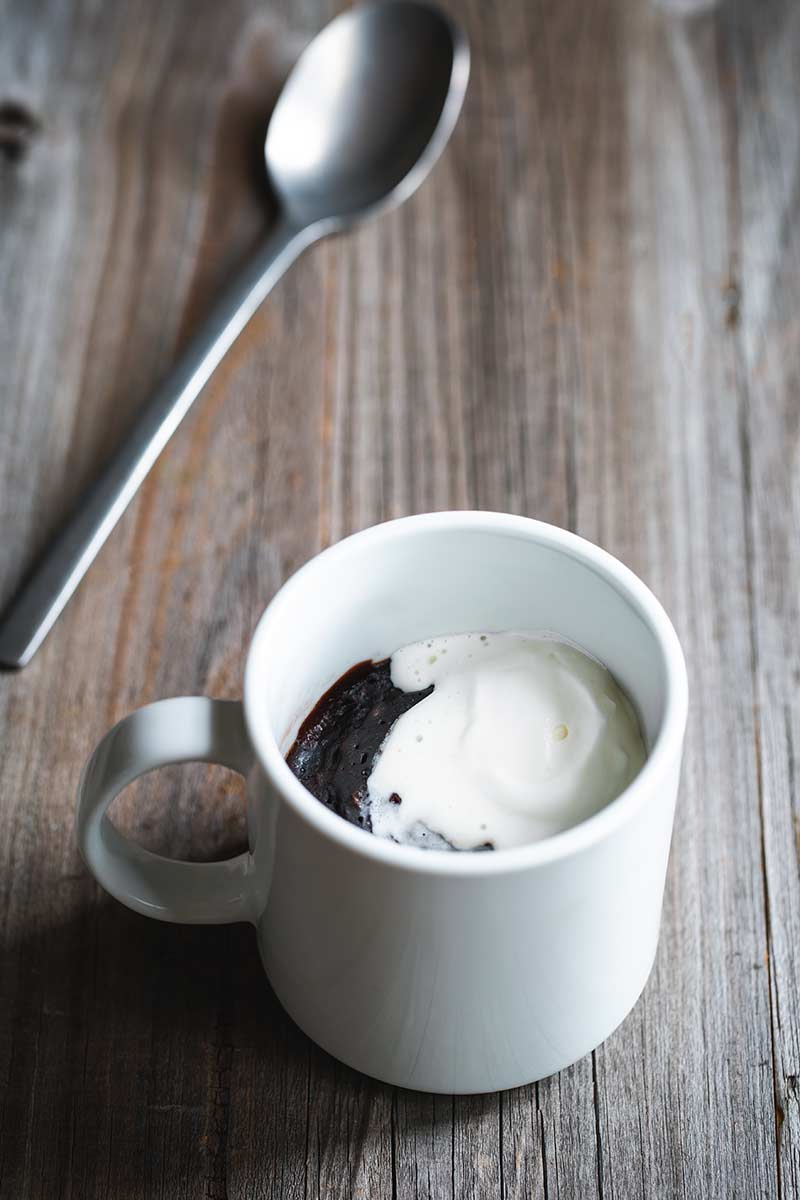 brownie in a mug topped with whipped cream next to a spoon
