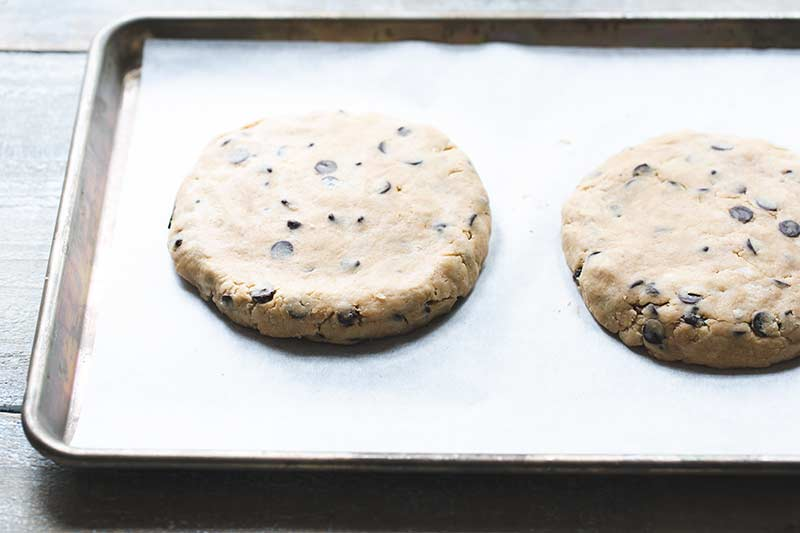 Dough formed into two round discs on a sheet pan lined with parchment