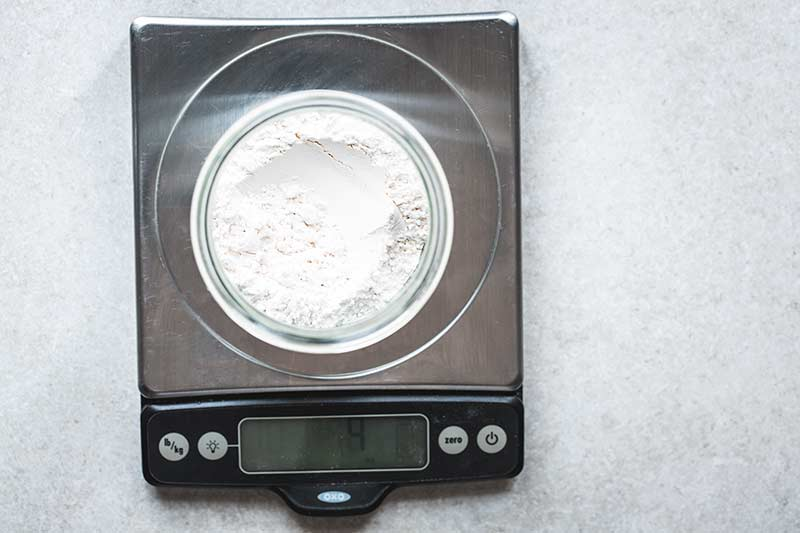 Flour measured out in a jar set on a digital scale