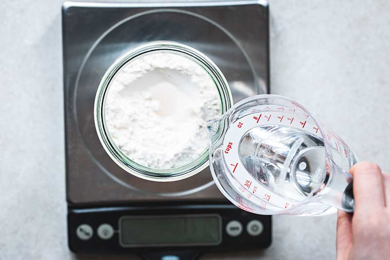 water poured into a jar with flour set on a digital scale