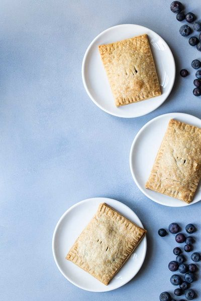 Three blueberry pop tarts on plates, surrounded by blueberries