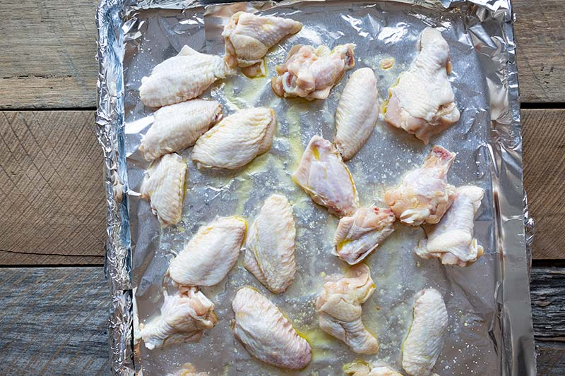 Chicken wings on a sheet pan lined with foil.