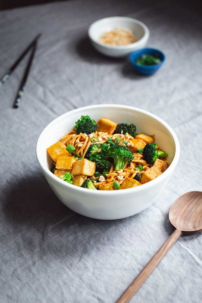 Spicy noodles with tofu and broccoli in a serving bowl next to a wood spoon.