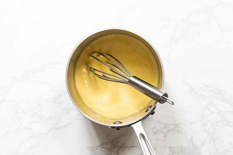 a saucepan with egg yolks and sugar whisked together