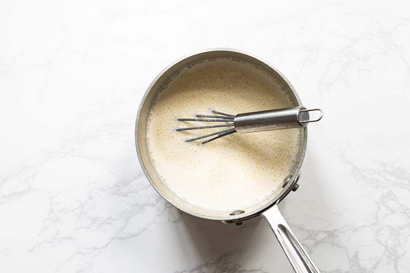 Cream and milk whisked into egg yolk mixture