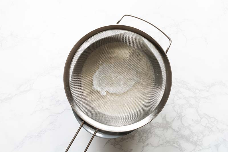 Cooked gelato base strained through a fine mesh strainer to remove lumps
