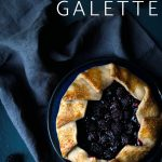 Blackberry galette on a plate surrounded by blackberries