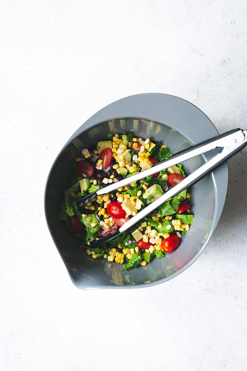 edients for salad in a bowl with tongs