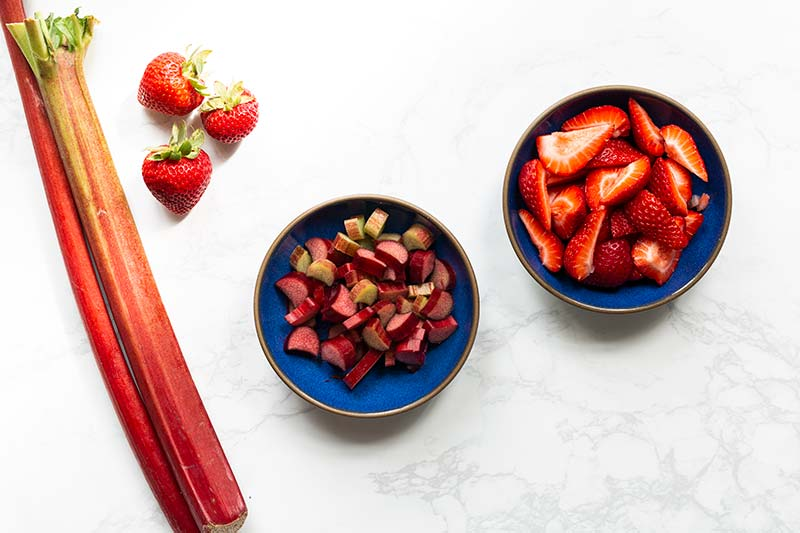 Chopped strawberries and rhubarb in separate blue bowls