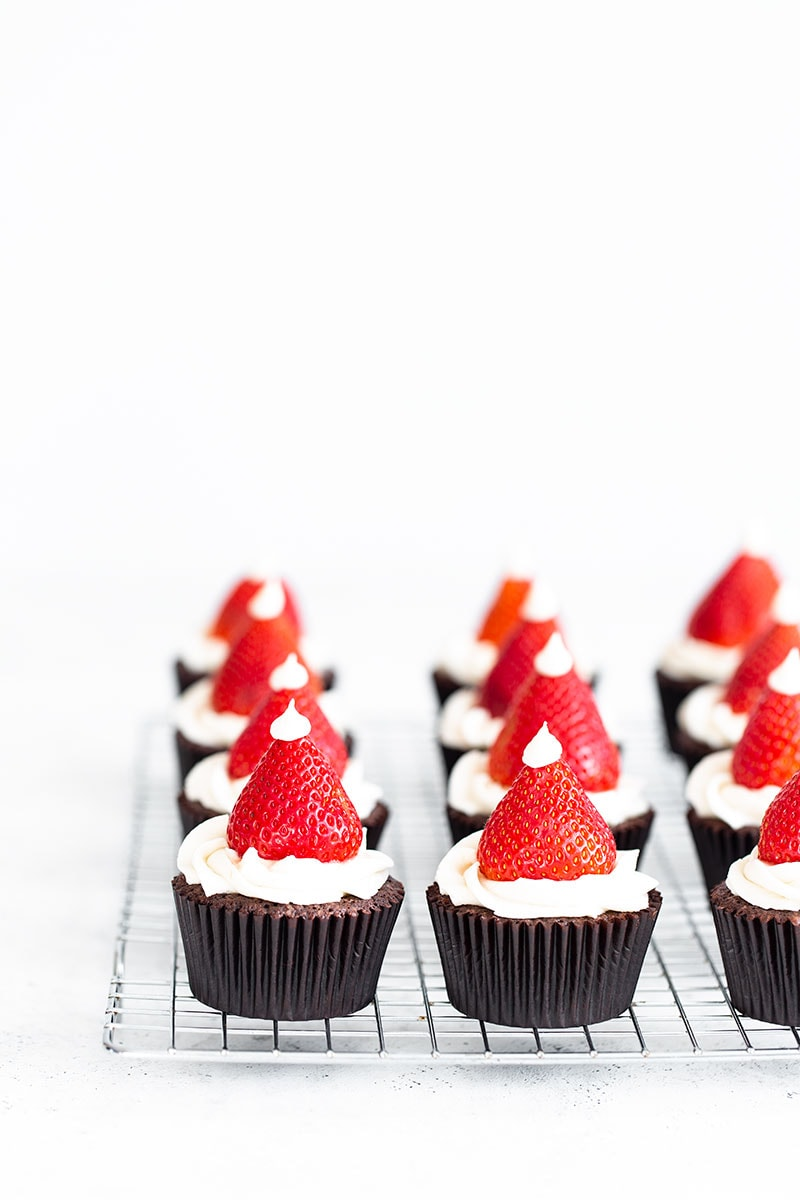 9 Santa Hat Cupcakes on a cooling rack