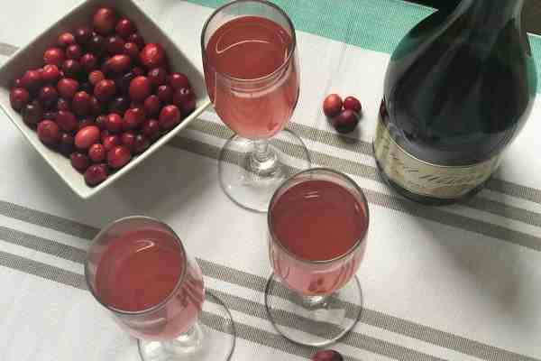 Cran - Mango Mimosa with cranberries and Champagne bottle.
