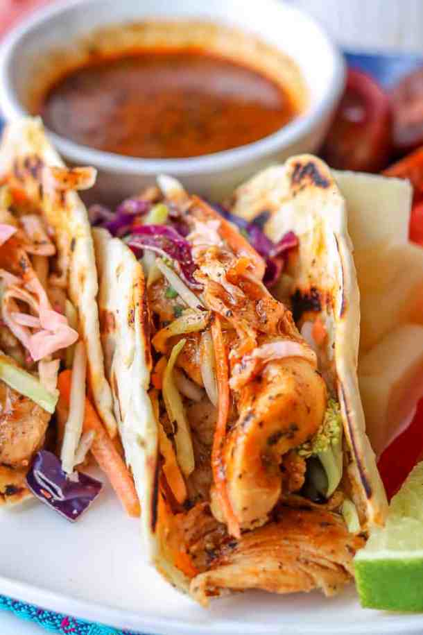 Set of Haitian Chicken Tacos toped with pikliz, sauce in the background.