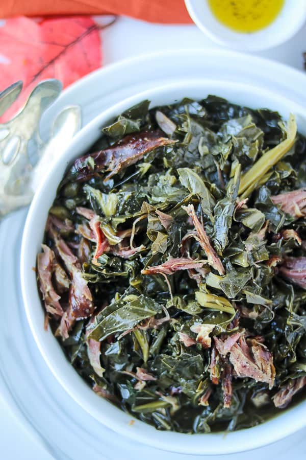 pressure cooked Instant pot collard greens with smoked turkey neck in white bowl