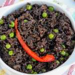 Haitian Black Rice in white bowl topped with red bell pepper and green peas.
