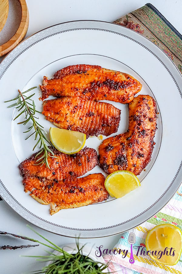 3 pieces of blackened tilapia fish with 2 slices of lemon and rosemary
