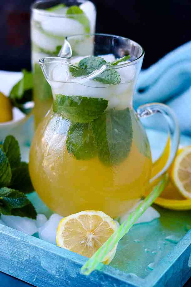 Haitian Jus Citron In glass pitcher with mint and lemon halves