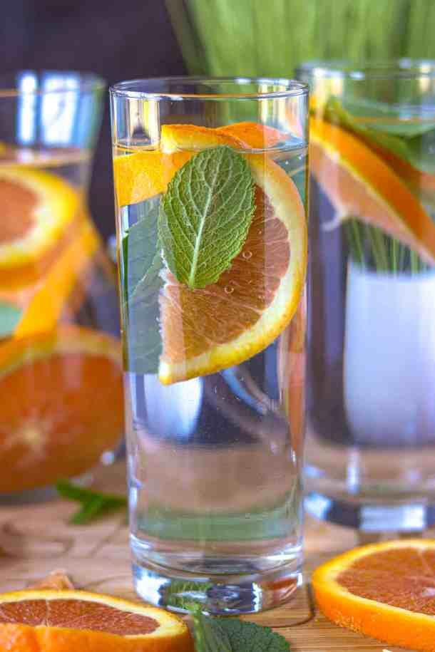 orange and mint in tall glass with slices of oranges on cutting board